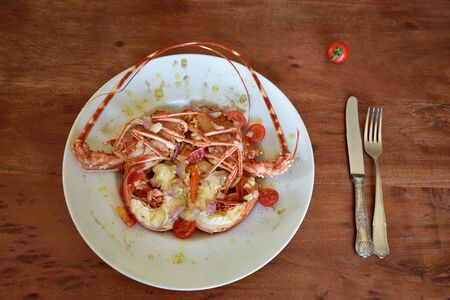 Salad of a boiled crawfish garnished with olive oil on a plate standing on a brown wooden table in Sicily and cutlery