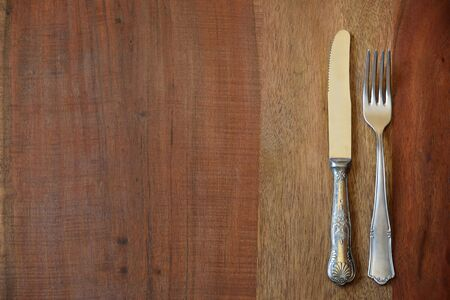 Background from a table top of a rustic wooden table on which lie an old decorated fork and an old decorated knife