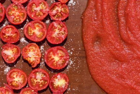 On a wooden board lie sliced ​​tomatoes with salt and dried and tomato sauce for the traditional preparation of tomato concentrate in the sun on Sicily