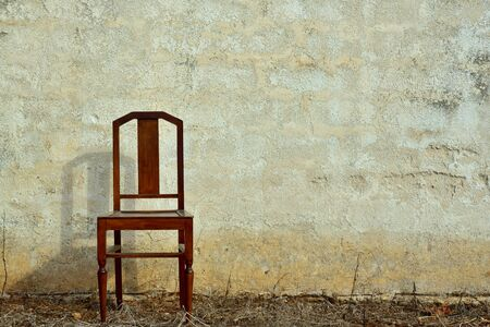 An old wooden chair stands on dry land in front of an old rustic plastered bright wall in Sicily