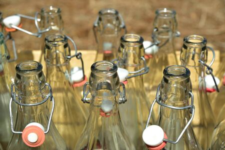 A wooden box with empty glass bottles stands outdoors on a dry meadow in summer