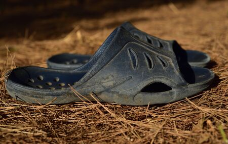 used old dirty plastic shoes stand on a dry meadow in summer