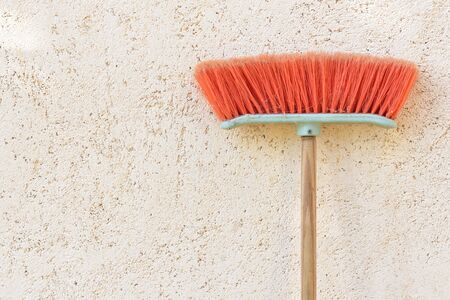 A used plastic red broom leans with bristles facing up on a plastered wall with text box Stock Photo