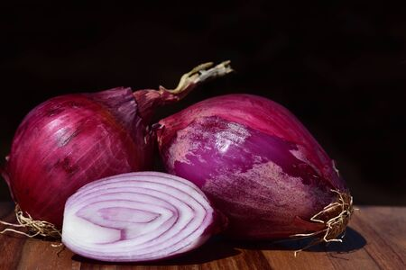 Still life with red onions lying side by side on a table for cooking in Italy