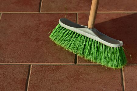 A green used broom with bristles cleans the floor on brown tiles as background