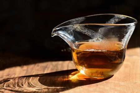 Close-up of a Chinese glass teapot with black fresh tea standing on a table against a dark background with the sunlight shining through it Banco de Imagens