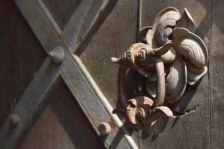 historic old brown wooden door with metal fittings and historic door knocker outdoors Stockfoto