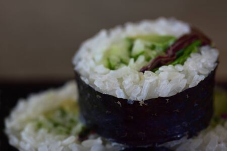 Japanese food with a thick roll futomaki, which is filled with vegetables, rice and algae leaves encased