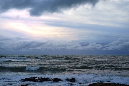 Next view of the churning sea in the evening with dark menacing clouds and the sun setting as background Stock Photo
