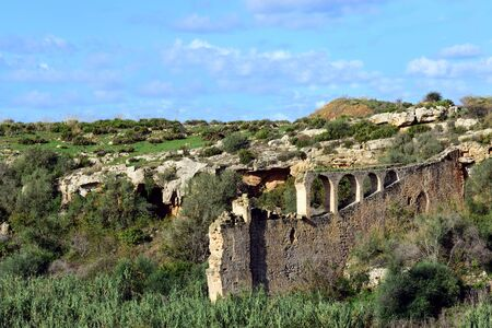 Typical landscape on Sicily with dilapidated ruin in the foreground between wild vegetation