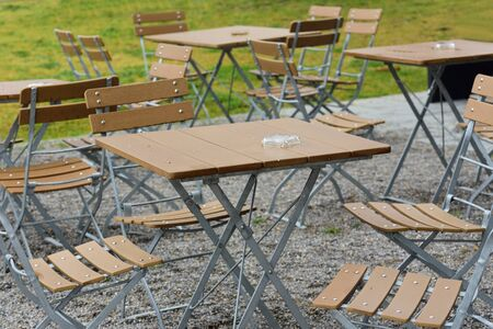 Scene of empty wooden tables and chairs of a restaurant outside after the rain and without guests in Germany