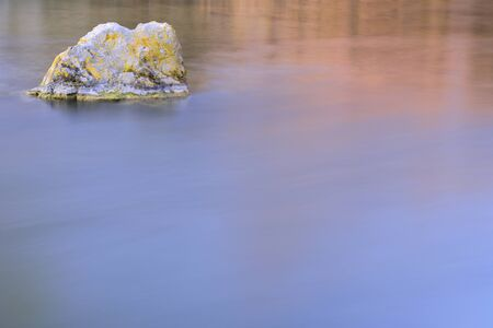 A single rock is on the edge of calm water in the morning at sunrise with plenty of space for text and water as a background