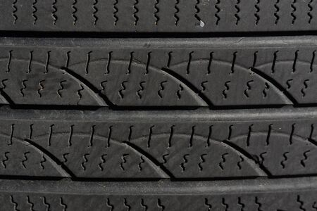 Dark background of a detail of an old worn car tire with very poor profile Фото со стока