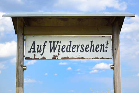 """On a white weathered sign reads """"Auf Wiedersehen"""" in German, against a blue sky with clouds."""