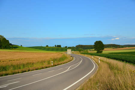 In Bavaria in summer a road leads through the fields and forests against a blue sky
