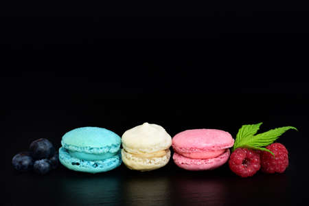 Three sweet macarons, in the colors of the French flag, lie side by side against a dark background, with blueberries and raspberries