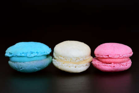 Three sweet macarons, in the colors of the French flag, lie side by side against a dark background