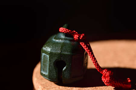 On a round plate made of cork stands a green metal bell, with a red cord on it, against a dark background