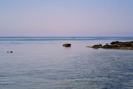 Background with the sea, small rocks in the water, the horizon and the sky, which shimmers slightly reddish in the morning. A small boat is sailing on the water 版權商用圖片