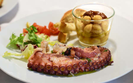 A starter of Mediterranean polyp salad and chickpea salad is served on a white plate
