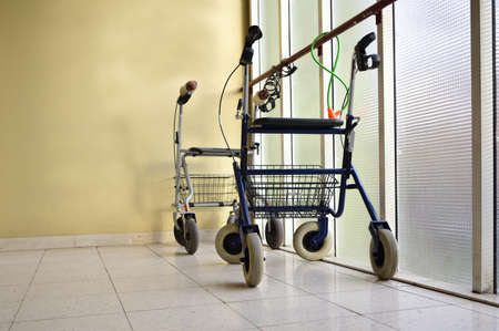 In a desolate corridor, two walking aids for elderly people are chained to a glass wall, in front of a stained house wall and on a tiled floor
