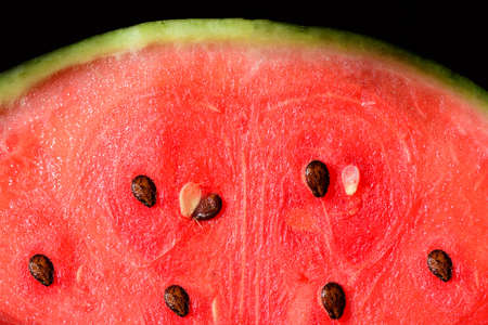 Close-up and texture of a sliced watermelon, with red flesh and the kernels, against a dark background