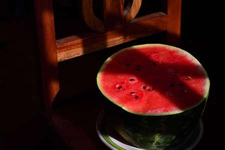 A freshly sliced melon half lies on a wooden chair in a dark, shady room