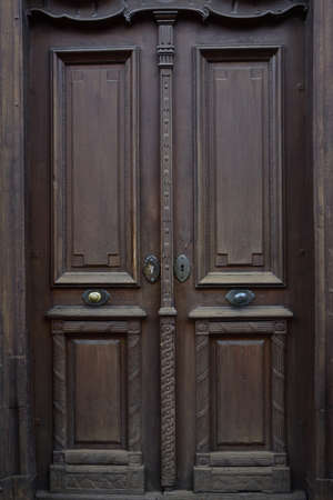 Background of a dark brown historical door with wooden decorations, which is made of wood