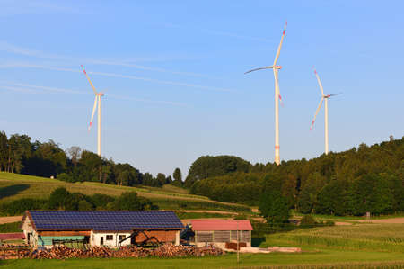 On August 25, 2021, the evening sun shines on a farm near Augsburg, Germany, on whose barn there is a solar system. In the background a lot of nature, sky and three large wind turbines