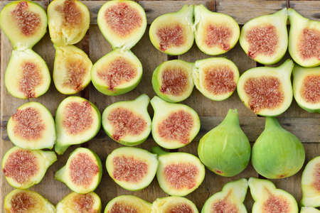 Background of many freshly sliced figs lying next to each other on an old wooden box