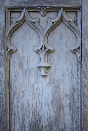 Background, texture and detail of an old blue wooden door with ornament and space for text, in portrait format