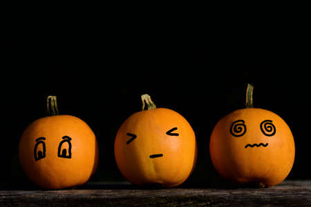 Three small orange pumpkins with different faces against a dark background with space for text