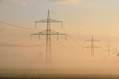 In autumn in the morning the sun rises behind high electricity pylons, in front of fog and a red sky in Germany