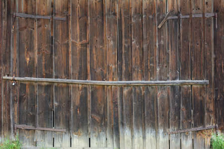 Background and detail of an old barn door made of brown wood with signs of weathering, which is closed.