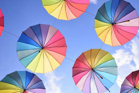 Colorful umbrellas in the colors of the rainbow hang in the air next to each other against a blue sky