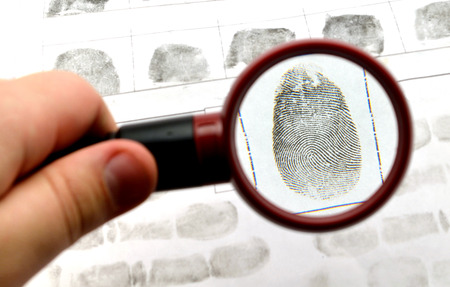 revealing tracks: comparing the fingerprint through the dactyloscopic magnifier glass Stock Photo
