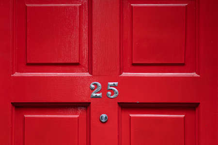 Detail of a red door with number 25 and peephole Archivio Fotografico