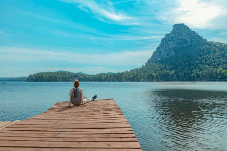 Lonely young girl sits on a pier against the backdrop of mountains and forest