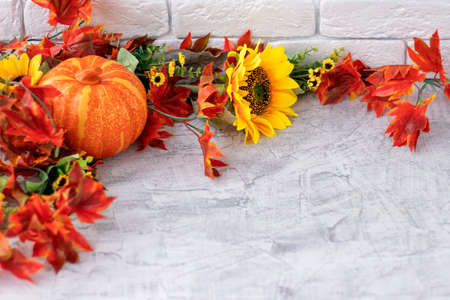 Beautiful autumn still life with sunflowers, red- yellow flowers, autumn leaves and orange pumpkin on white brick wall background. front view. Autumn concept with pumpkin and flowers. copy space Soft focus. 写真素材