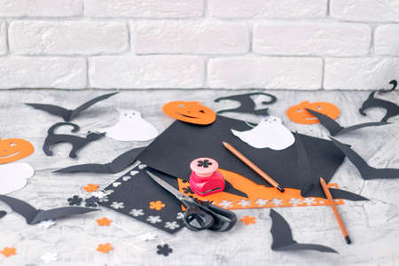 Preparation for Halloween Decoration for the holidays, cutting from colored paper on a white brick wall. orange and black colored paper, scissors, pencils, figured hole punch Soft focus. 写真素材