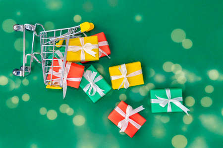 A fallen small cart with scattered gifts. Red, green and yellow gifts in a shopping trolley on green background with bokeh. Christmas and Christmas gift concept. Top view