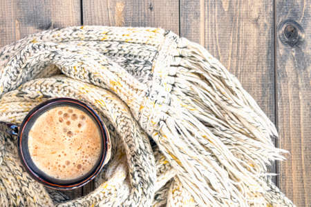 Cup with of hot coffee with foam on a rustic wood table background wrapped in warm knit wool scarf. Mug of cappuccino. Concept of Winter, heat, holidays and events. Soft focus. Top view.