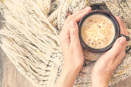 Female hands hold cup of hot coffee with foam on wooden table with warm knit woolen scarf. Mug of cappuccino. Christmas background.Concept of winter, warmth, holidays, events.Soft focus.Top view.Toned Stock Photo