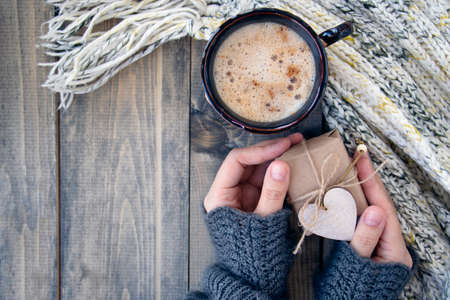Female hands hold little gift near cup with a hot drink on of wooden table with warm knit woolen scarf. Christmas background - The concept of winter, warmth, holidays and events. Top view
