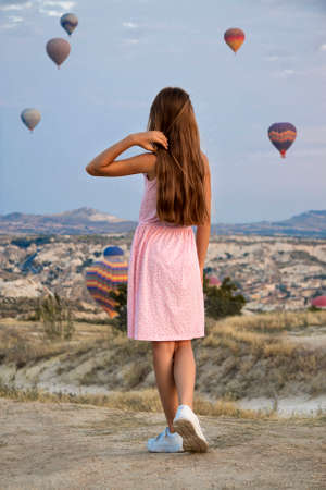 A young girl looks at balloons in Cappadocia, Turkey.