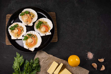 Scallops, lemon, garlic, parsley, butter and salt on black background. Baked scallops with caviar and creamy garlic sauce in frying pan. Recipe for cooking scallops with caviar. Top view. Copy space