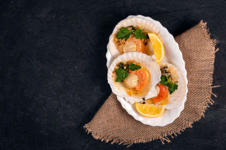 Baked scallops with caviar and creamy garlic sauce in white plate. Scallops with lemon on black background with napkin. Top view. Copy space. Flat lay