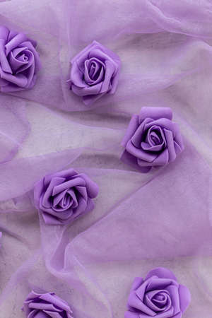 fake purple roses on chiffon fabric in purple or lilac color for backgrounds. top view Фото со стока