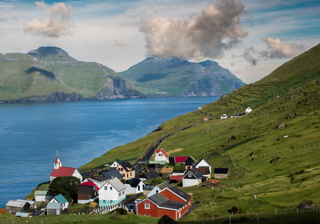 Kunoy town in Faroe Islands with cloudy sky and atlantic ocean in background