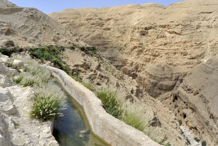 Ancient water conduit in Qelt gorge,  Judea desert